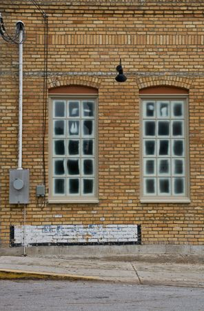 meter box: Windows in a yellow brick wall with lights on wall and meter box