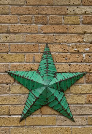 Partially rusty five point primitive star with flaky green paint