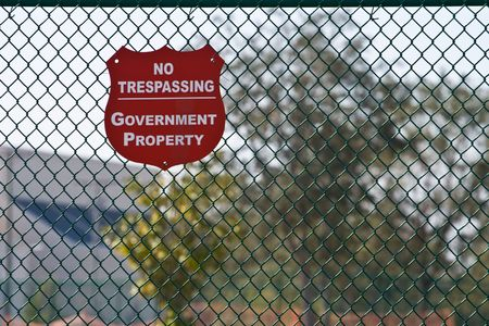 Red shield No Tresspassing sign marking government property