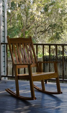 antique chair: Old wooden rocking chair sitting on a porch