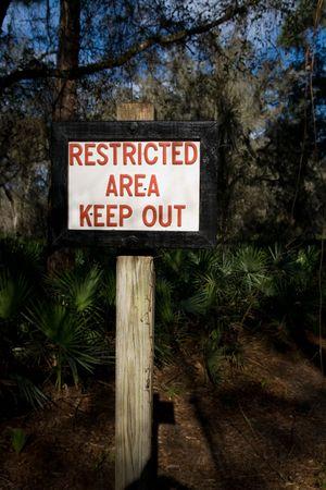 area restringida: Signo que indica una zona restringida en el bosque a lo largo de un camino