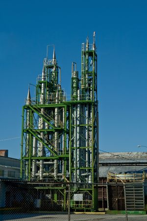 Cooling towers at a factory surrounded by bright green steel frame