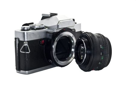 heavily: Heavily used, slightly grimy and beatup SLR camera with lens detached and a white background