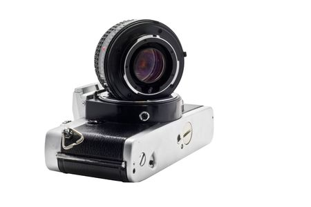Heavily used, slightly grimy and beatup SLR camera with lens detached and a white background photo
