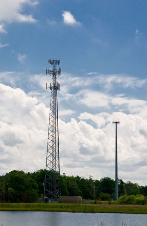 Cell towers against partly cloudy sky across the river Banco de Imagens