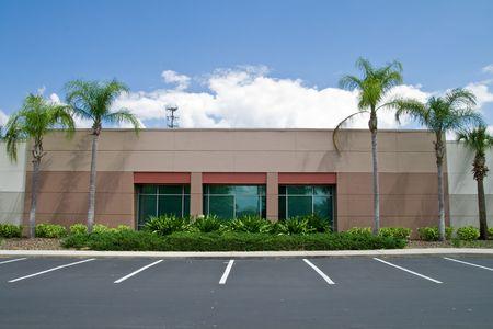Kant van kantoorgebouw met parkeerplaatsen en palmbomen
