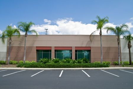 Side of office building with parking spaces and palm trees