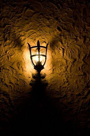wall sconce: Dim Estilo Antiguo Antorcha Sconce en Dark Room, que ilumina s�lo una peque�a cantidad de pared.  Foto de archivo