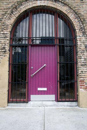 バーのアーチ道の鉄とガラスで紫色のドア