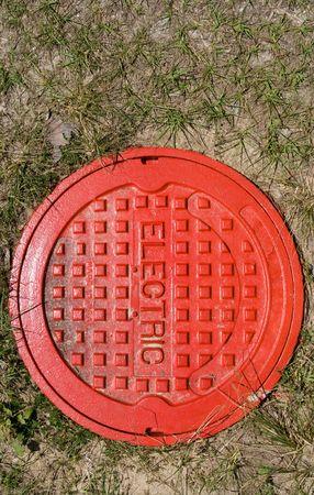 真っ赤な草で電気マンホール カバー 写真素材
