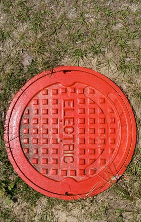Red painted electric manhole cover in grass Stock Photo