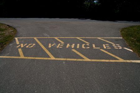 No vehicles warning painted on asphalt leading to bike path