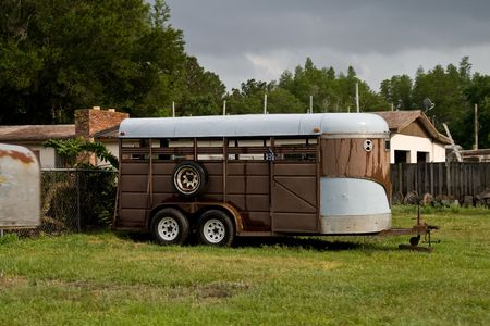 Old brown horse trailer parked on the grass at a small ranch