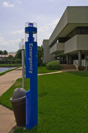 Emergency phone pole next to modern building with nice lawn
