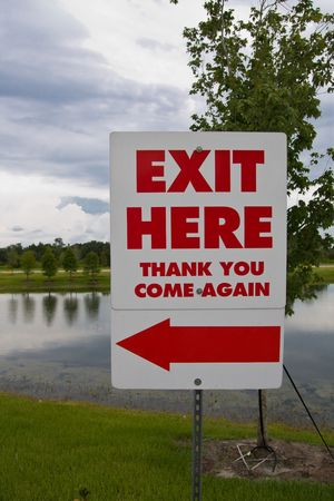 Exit here sign with red arrow and pond in background Banco de Imagens