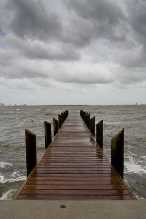 Vertical oriented image of a wooden pier on an stormy afternoon with looming dark clouds 免版税图像