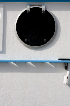 sidewall: Closed and sealed porthole window on the sidewall of a boat