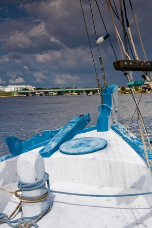 Forward view of the bow of a small fishing boat with bowspirit and rigging on a stormy afternoon right before it started raining Stock fotó