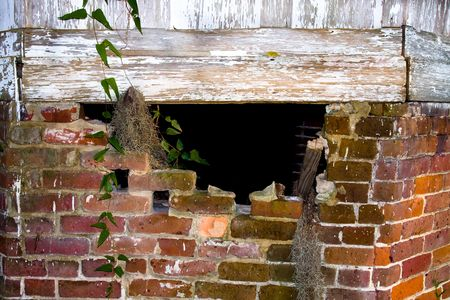 Hole in the crumbling brick foundation of an old house