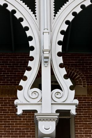 workmanship: Symmetrical white ornate wooden column on old moorish style building in front of brick wall and window Stock Photo