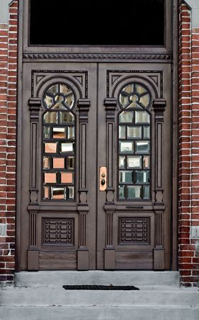 Ornate antique doors with windows in brick wall