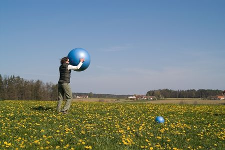 yuong girl plaing with big ball on the spring meadow photo