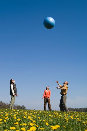 Three yuong peple plaing with big ball on the spring meadow photo