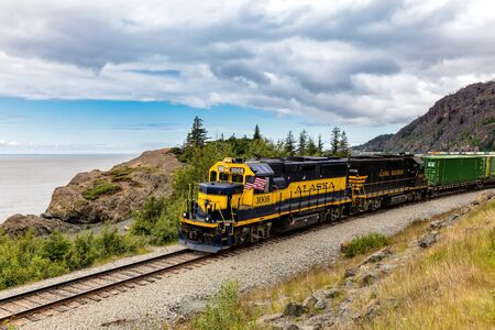 Black and yellow train moving down the track in Alaska