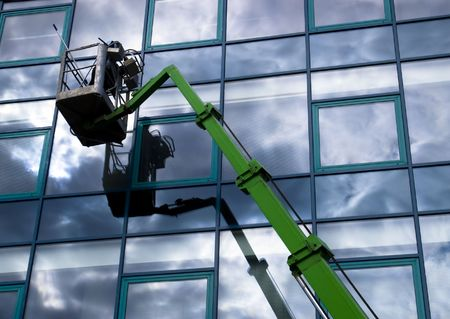 cleaning an office: Window cleaner working on a glass facade in a gondola