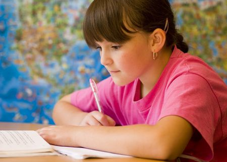 solve problems: Concentrated young girl doing her school home-work. Stock Photo