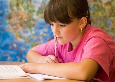 concentrated: Concentrated young girl doing her school home-work. Stock Photo