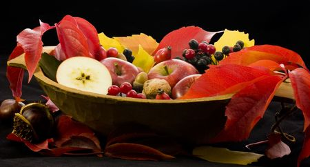 A basket of multi-colored leaves  with apples photo