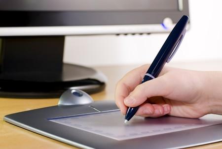 Hand holding pen on wireless tablet Standard-Bild