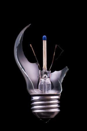 A broken lightbulb with a  match inside photo