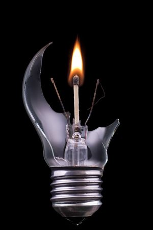 A broken lightbulb with a burning match inside