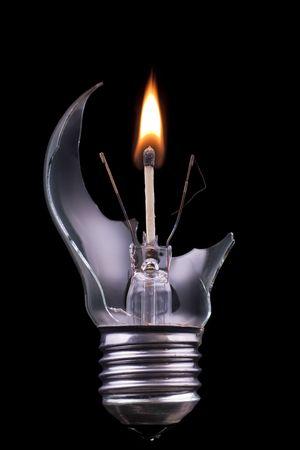 A broken lightbulb with a burning match inside