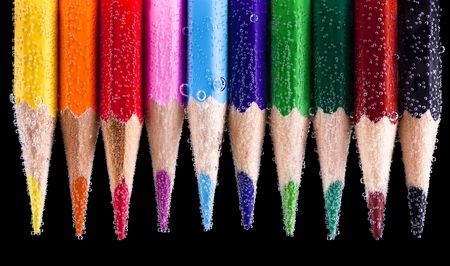 Color wood pencils with bubbles on black background photo