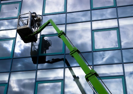 blue facades sky: Window cleaner working on a glass facade in a gondola