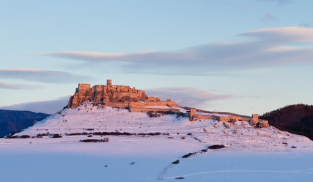 Sunset and castle in winter. Medieval castle in Slovakia, central europe photo