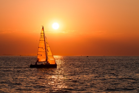 fishing scene: Sailing boats on a background of a beautiful sunset