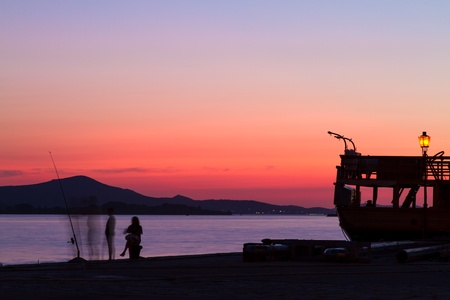 silhouette of fishermen with  orange sunset Stock Photo - 13028507