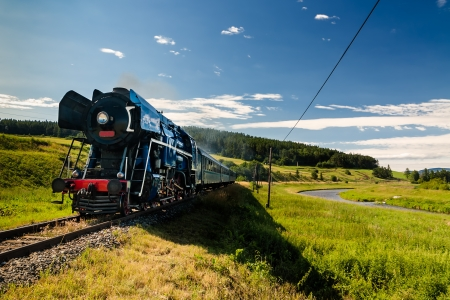 Steam engine locomotive train moving next to the river photo
