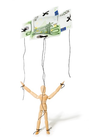 puppeteer: concept, a puppet controlled by money, giving it freedom Stock Photo