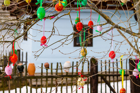 folk village: Easter eggs on a tree in front of wooden cottage  Slovakia
