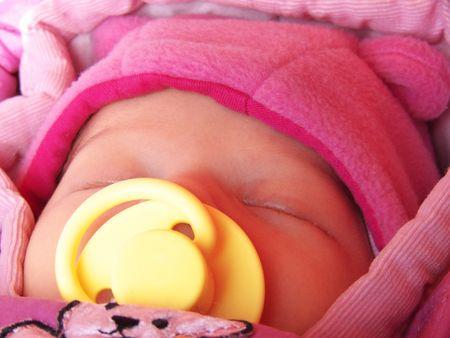 Newborn baby girl sleeping with yellow dummy
