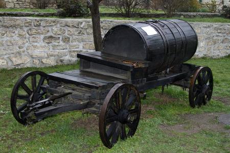 temple tank: Old wooden barrel on cart. Vintage black barrel wagon transports water.