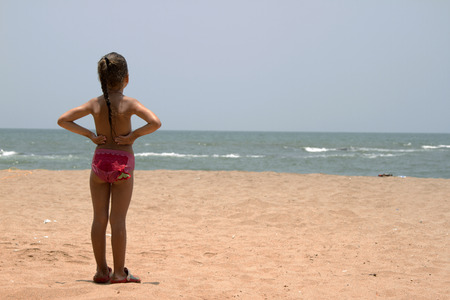 beach blond hair: Beautiful little girl standing on the sandy beach. India, Goa.