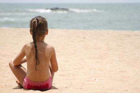 beach blond hair: Beautiful little girl sitting on the sandy beach. India, Goa.
