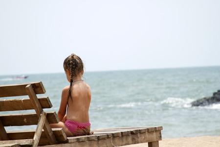 Beautiful little girl sitting on a lounger sandy beach. India, Goa.