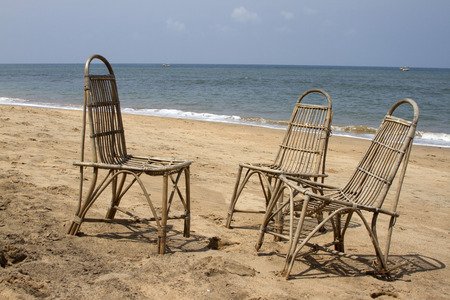 Three wattled chairs stand on a beach, wait for people against the sea. GOA India beach. photo